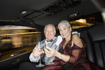 Well dressed senior couple drinking champagne in limousine