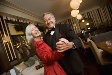 Well dressed senior couple dancing in restaurant