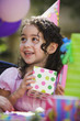Hispanic girl opening gift at outdoor birthday party