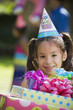 Hispanic girl carrying gifts at outdoor birthday party