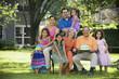 Three generation Hispanic family posing for portrait in backyard
