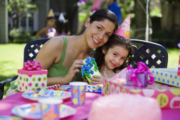 Hispanic mother giving gift to daughter at outdoor birthday party