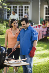 Hispanic couple grilling in backyard