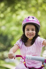 Hispanic girl riding bicycle outdoors