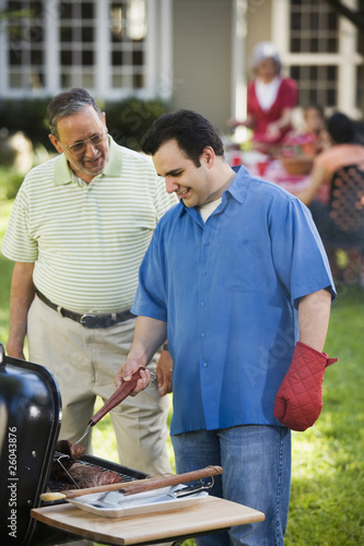 Hispanic father and adult son grilling in backyard
