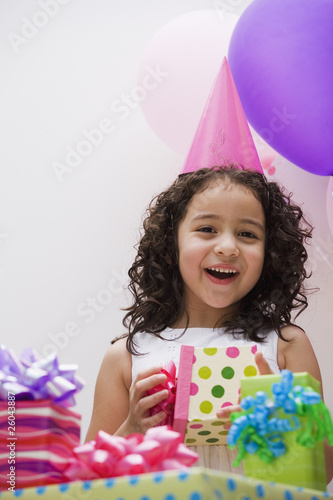 Hispanic girl opening gift at birthday party