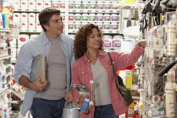 Hispanic couple shopping for painting supplies