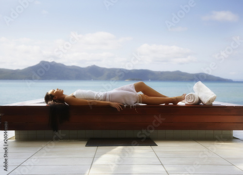 Pacific Islander woman laying next to water