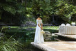 Pacific Islander bride standing at the edge of a pond