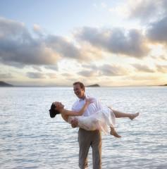 Man carrying woman at beach