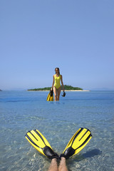 Pacific Islander woman holding snorkeling gear in ocean