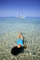 Pacific Islander woman laying in ocean
