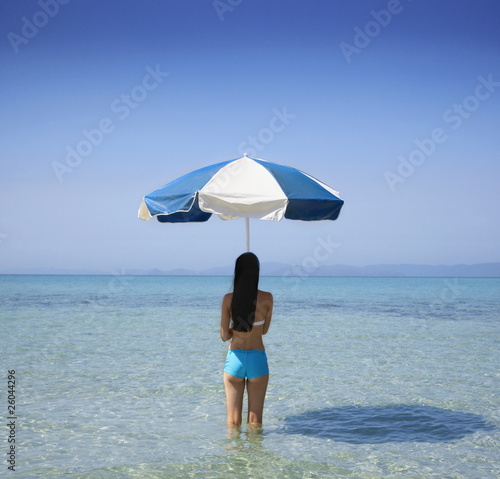 Pacific Islander woman holding beach umbrella in ocean