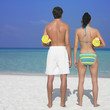Couple holding towels at beach