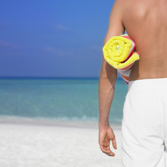 Man holding towel at beach