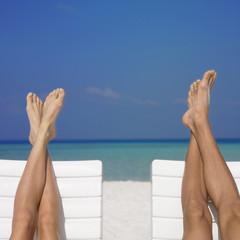 Couple's feet on beach chairs