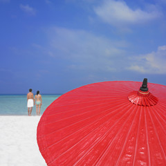 Couple on beach with umbrella in foreground