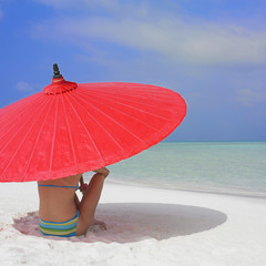 Woman sitting under umbrella at beach