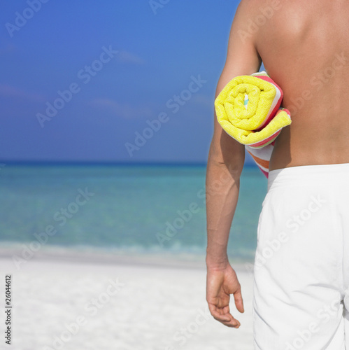 Man holding towel at beach