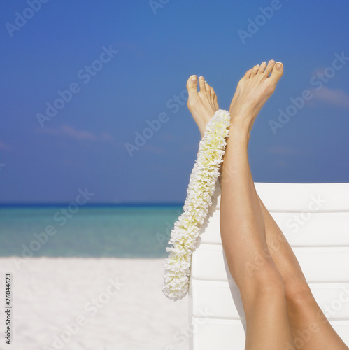 Woman's feet with lei at beach