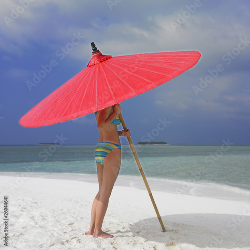 Woman standing under umbrella at beach