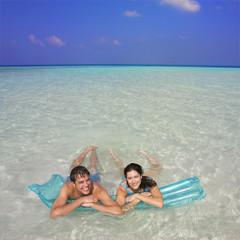 Couple on pool raft in ocean