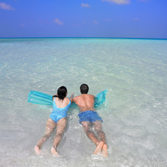 Couple on pool raft in ocean