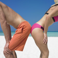 Couple touching rear ends at beach