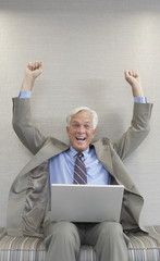 Businessman cheering and holding laptop