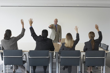 Businessman pointing at co-workers with hands raised