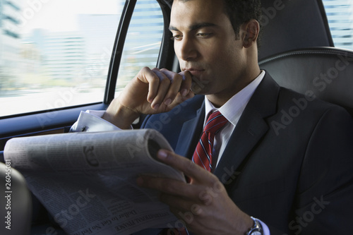Hispanic businessman reading newspaper in limousine