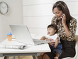 Hispanic working mother holding baby son and talking on phone