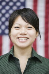 Asian woman standing near American flag