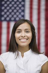 Hispanic woman standing near American flag
