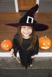 Mixed race young girl in witch costume with Halloween pumpkins