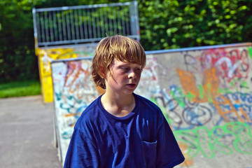portrait of young boy sweating at skate park