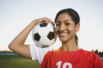Mixed race woman posing with soccer ball