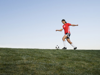Mixed race woman kicking soccer ball