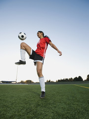 Mixed race woman bouncing soccer ball on knee