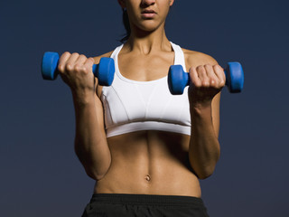 Mixed race woman doing biceps curls with dumbbells