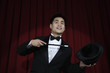 Asian magician in tuxedo pointing to top hat with wand