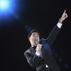 Asian man in tuxedo singing with arm raised