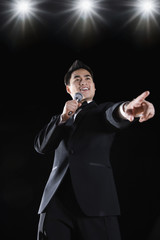 Asian man in tuxedo holding microphone and pointing
