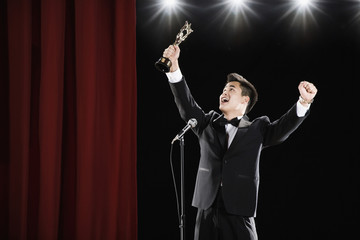 Asian man in tuxedo holding trophy overhead at microphone