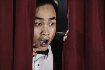 Asian man peering from behind red curtain and looking afraid