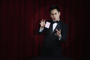 Asian magician in tuxedo doing magic trick onstage