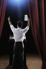 Asian man standing at podium with arms raised