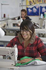 Mixed race woman using sewing machine