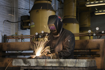 Welder working with torch in foundry