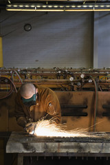 Hispanic welder working with torch in foundry